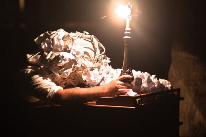person with paper for a head leaning on a desk holding a candlestick