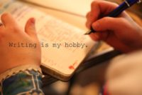hand writing in a notebook with caption writing is my hobby