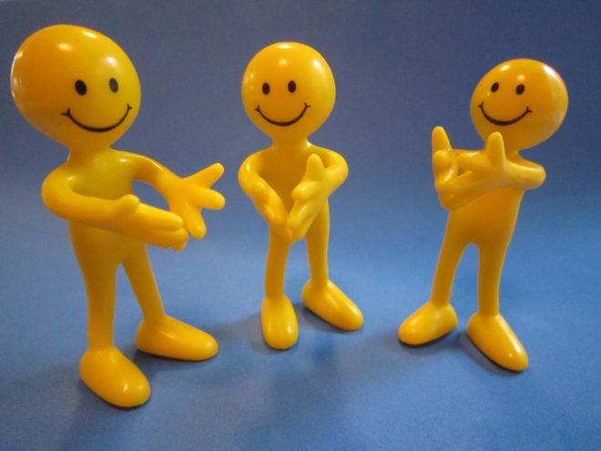 three yellow happy face heads with bodies clapping