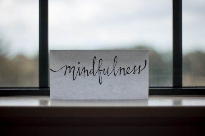 """Paper with """"mindfulness"""" written on it resting on a windowsill"""